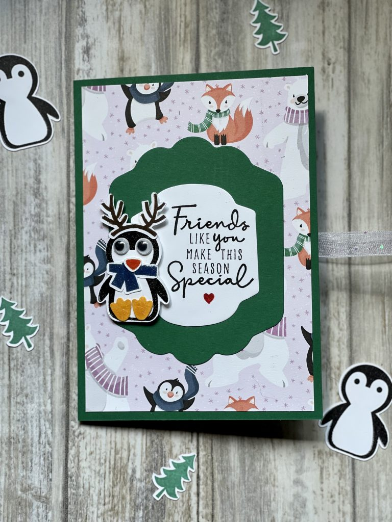 This is a card front showing a penguin with antlers on and google eyes on the background are foxes, penguins and polar bears made using the Penguin Place Bundle from Stampin Up!