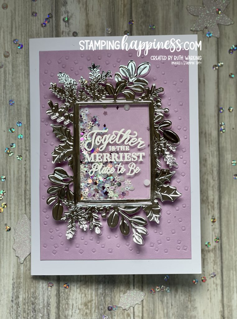 An image showing a Christmas card with a silver mirror frame and a white embossed greeting on acetate.  This card has a shaker box int he middle of the frame.  The background is Fresh Freesia card stock which has been embossed.  The card was created using the Merriest Moments bundle from Stampin Up