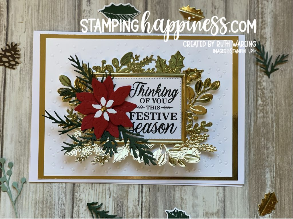 Image of a Christmas card showing a white background with fold embossed detail with a white panel saying Thinking of you this festive season and a red poinsettia with green foliage from the Merriest Moments bundle from Stampin up