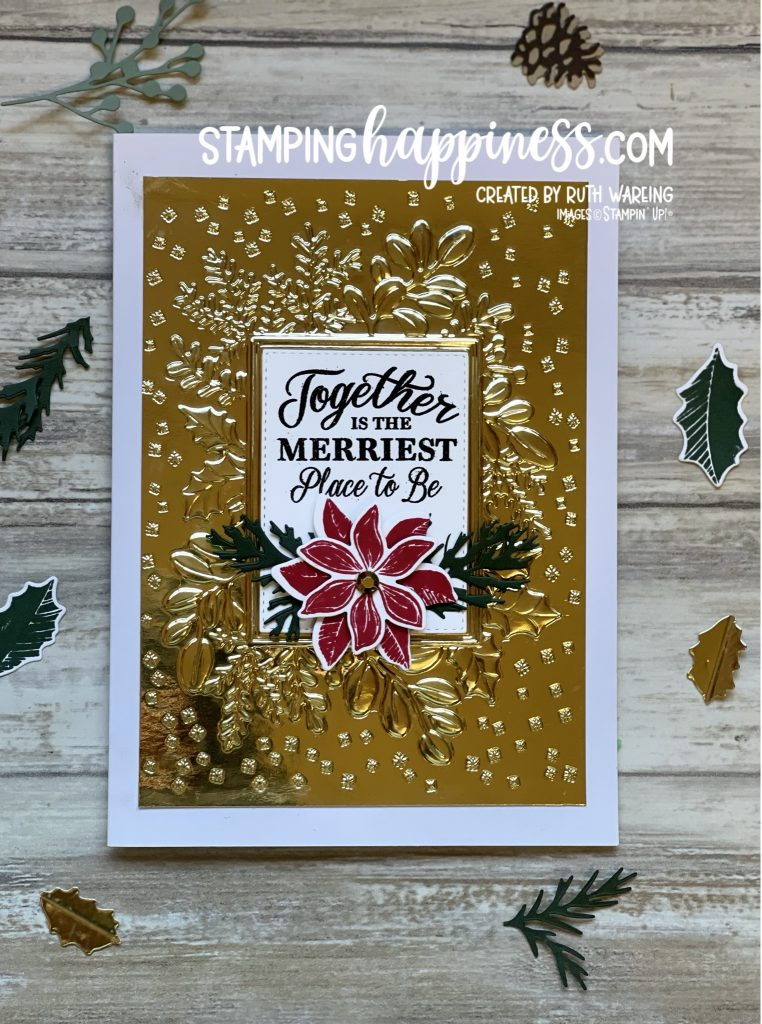 Image of a Christmas card showing a white background with gold embossed detail with a white panel saying together is the merriest place to be and a red poinsettia with green foliage from the Merriest Moments bundle from Stampin up