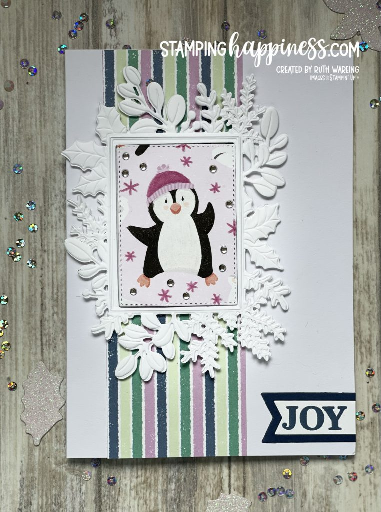 image of a Christmas showing a penguin within a white cut and embossed frame with holly and foliage around the edges with a stripey paper border behind on a white card base using the Merriest Moments bundle from Stampin Up