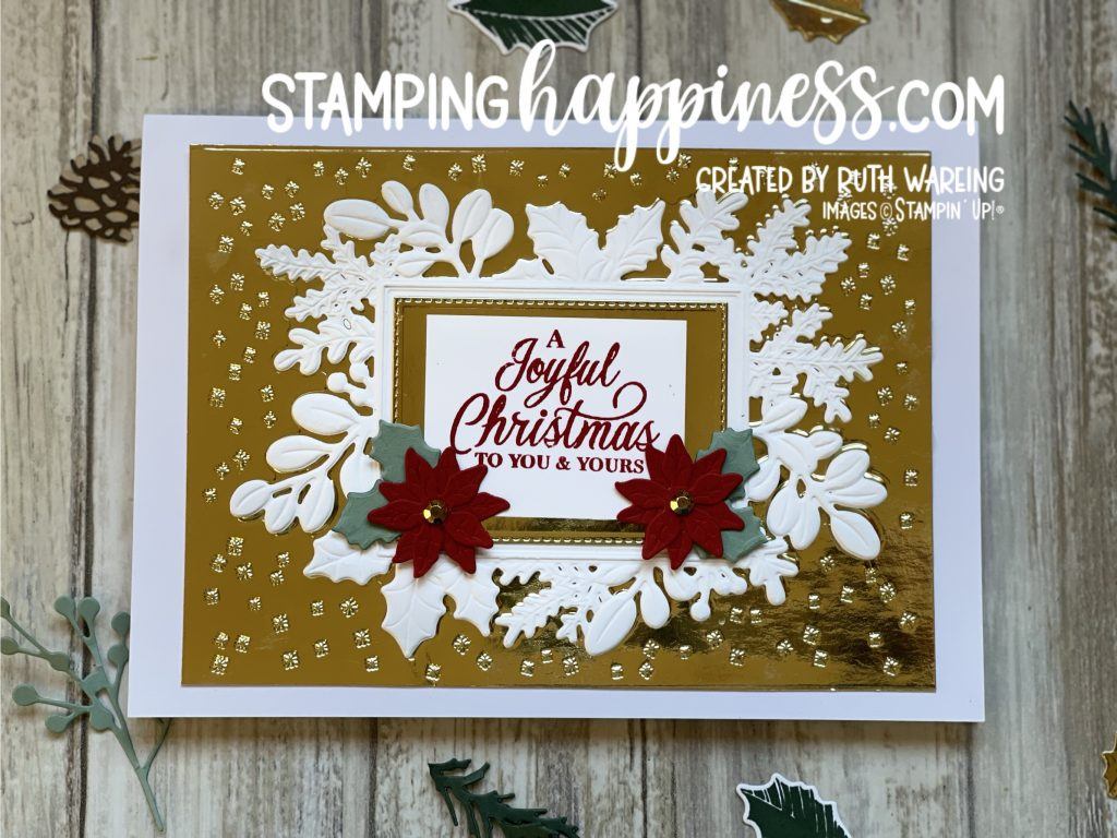 Image of a Christmas card showing a white background with gold embossed detail with a white panel saying A joyful Christmas to you and yours and 2 red poinsettia with green foliage from the Merriest Moments bundle from Stampin up